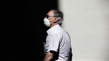 Una persona protegida con mascarilla recorre una calle en Valencia.
