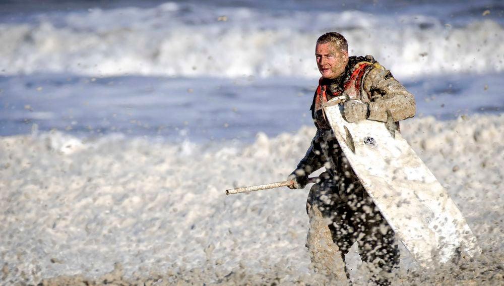 Un miembro del servicio de rescate sale del agua con una tabla