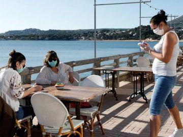 Personas en la terraza de un bar con mascarillas