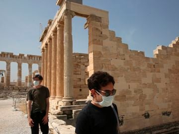 Dos turistas con mascarilla en la Acrópolis de Atenas