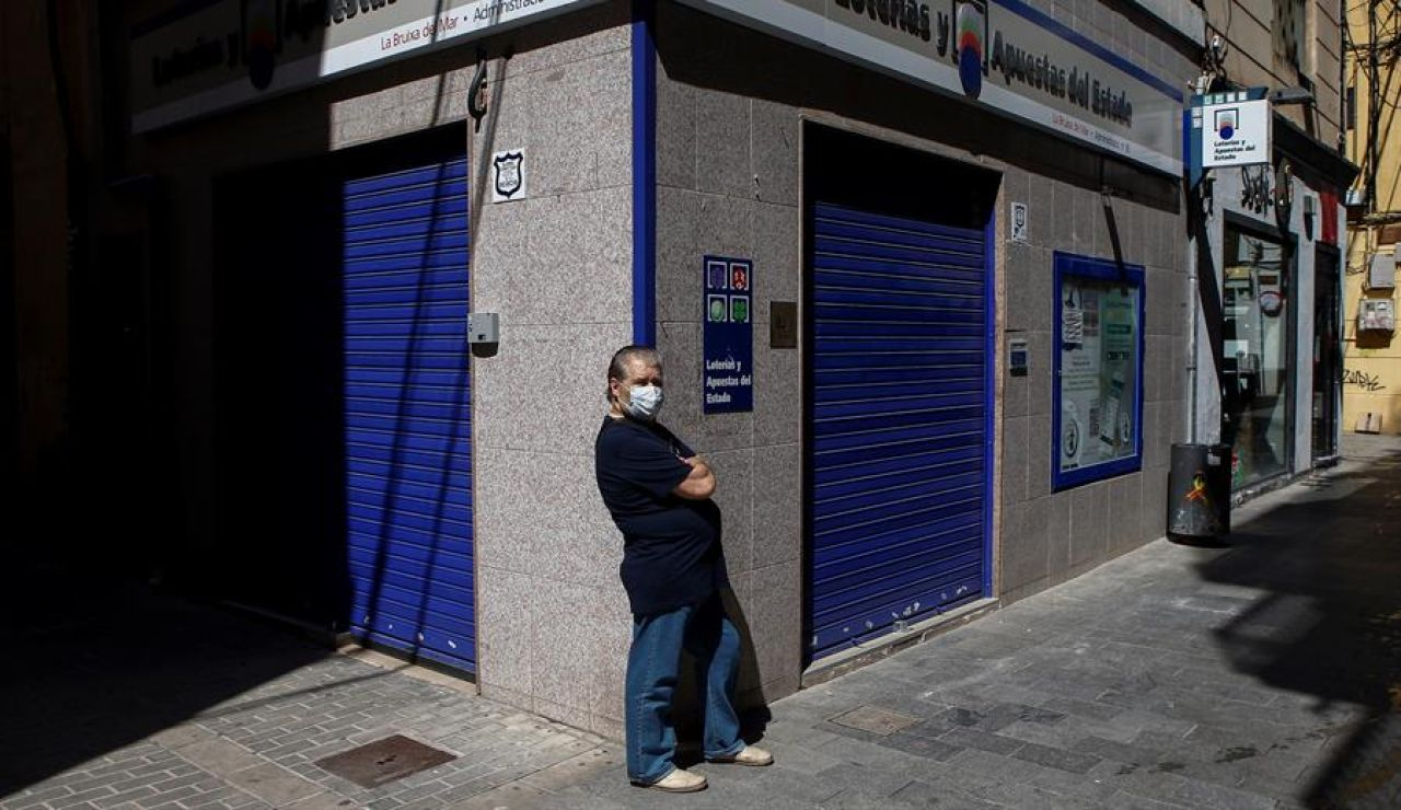 Un ciudadano con mascarilla frente a una administración de lotería en Barcelona