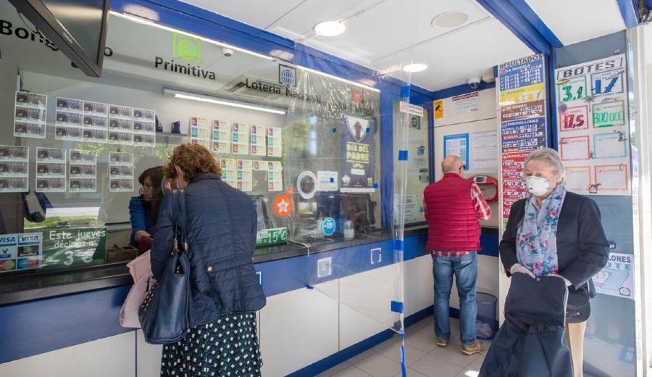 Varias personas acuden a una administración de lotería de Zaragoza este lunes