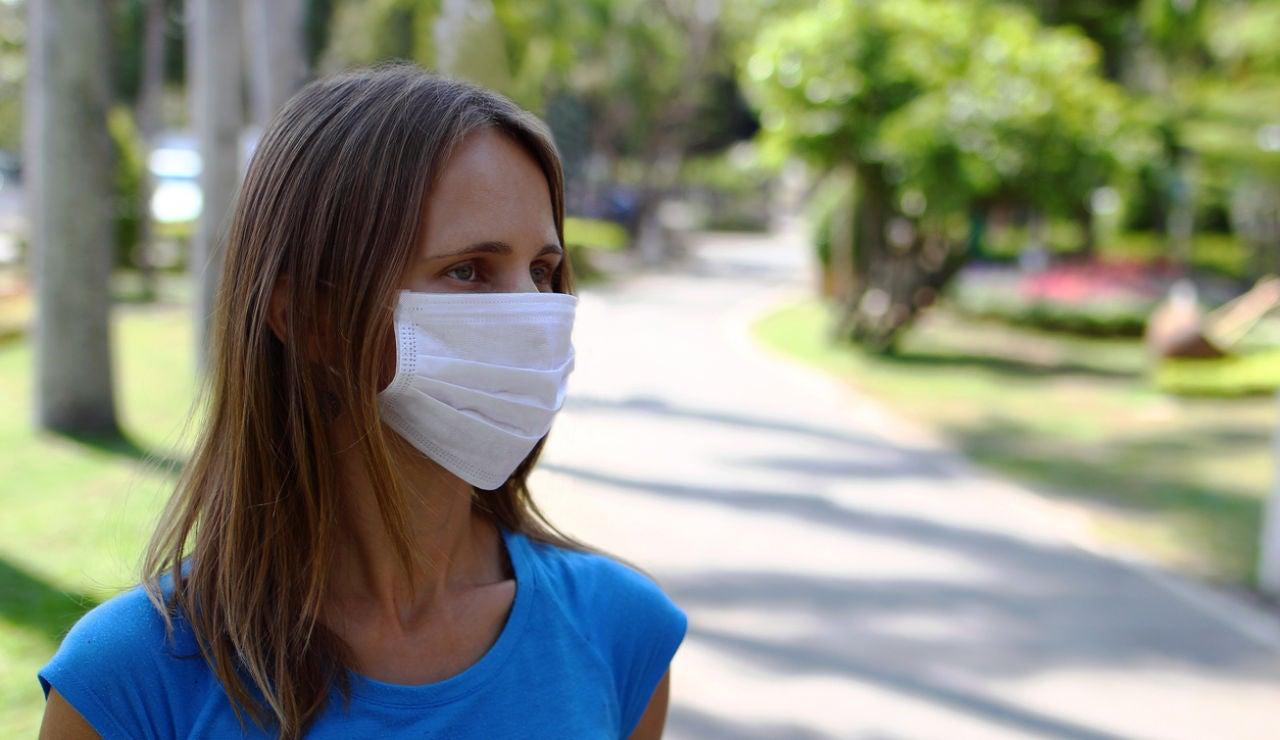 Una mujer en la calle con mascarilla