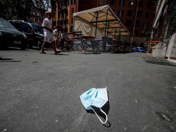Imagen de una mascarilla de protección tirada en el suelo en una calle de Roma
