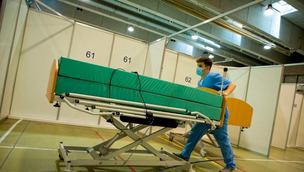 Un celador retira una camilla en un pabellón de Barcelona
