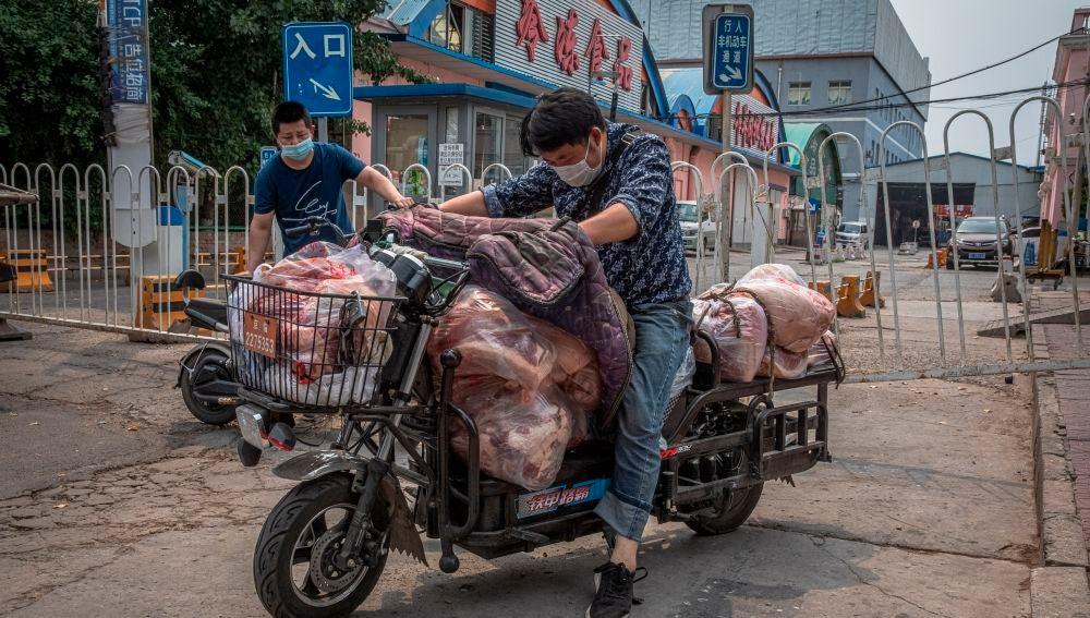 Un hombre con mascarilla montado en su moto en Pekín, China