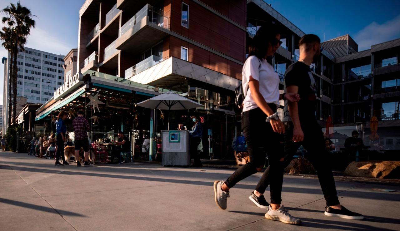 Turistas pasean por Santa Mónica, Estados Unidos, sin usar mascarilla