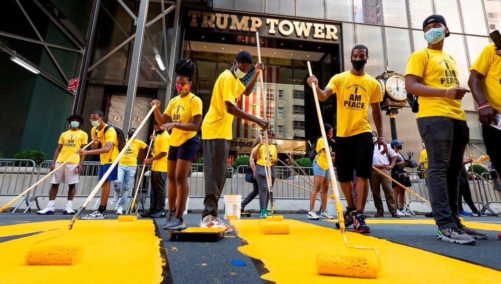 """Voluntarios ponen los toques finales al enorme eslogan amarillo de """"Black Lives Matter"""" en la calzada frente a la Torre Trump de Nueva York"""