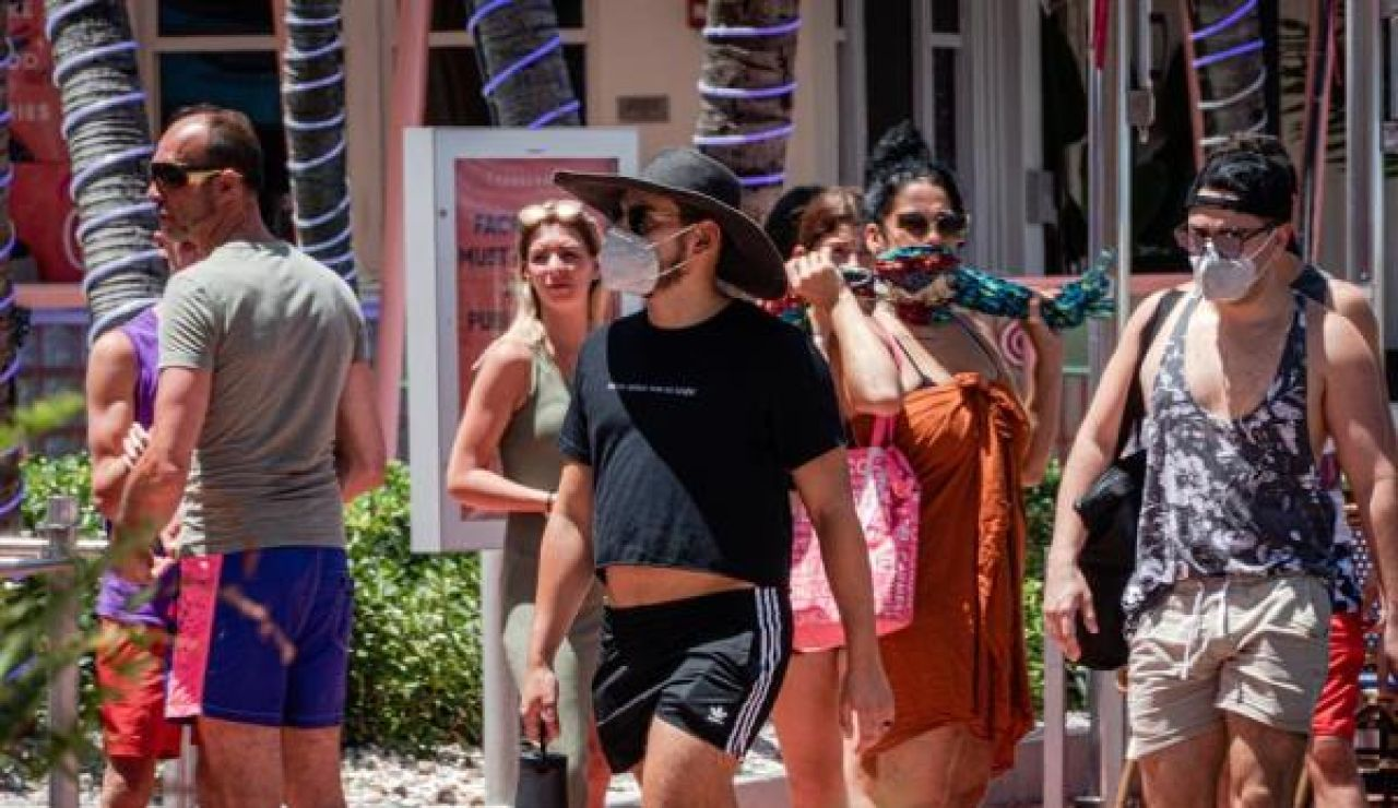 Un grupo de personas pasea con mascarilla por Miami