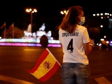Una aficionada del Real Madrid ante una Cibeles sin aficionados