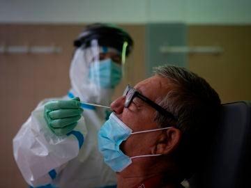 Una profesional sanitaria realiza una prueba PCR a un paciente en el CAP Raval Nord de Barcelona