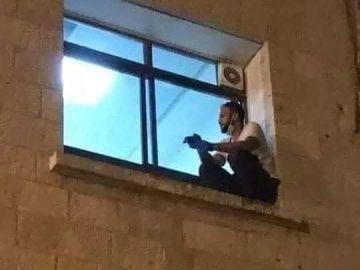 Un joven trepa por la fachada de un hospital en Cisjordania para despedirse de su madre fallecida por coronavirus