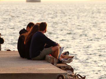 Un grupo de jóvenes charla al atardecer en una playa