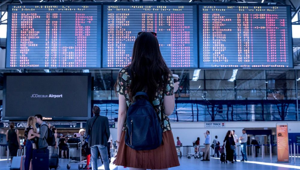 Chica en un aeropuerto mirando los vuelos
