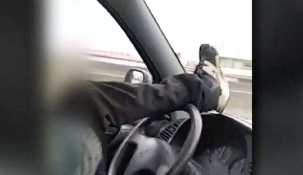 Dos jóvenes se graban conduciendo en dirección contraria y manejando el volante con el pie por una carrtera de Astillero