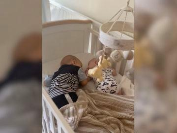 el bebé arropa a su hermano en la cuna