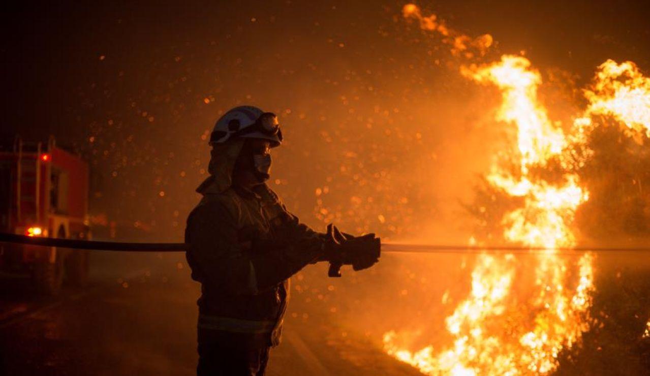 Varios bomberos realizan labores de extinción hoy domingo en el incendio forestal de Cualedro, Ourense