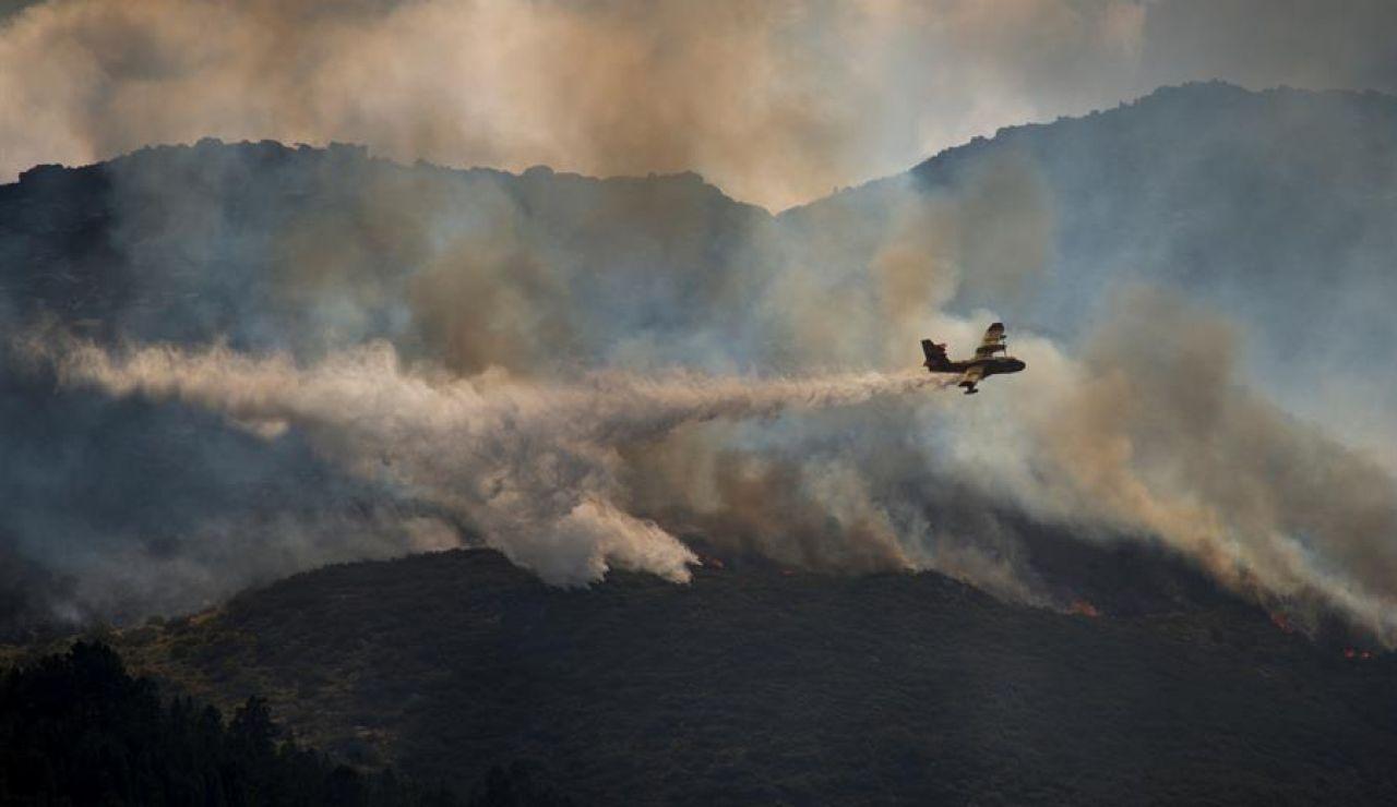 Una avioneta lanza agua sobre un incendio