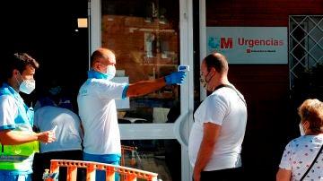 Un paramédico toma la temperatura a un ciudadano antes de acceder al centro de salud Reyes Católicos