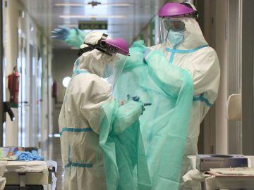 Sanitarios colocándose el traje EPI