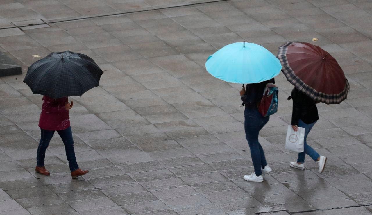 Escolares se protegen de la lluvia con paraguas este viernes en Bilbao