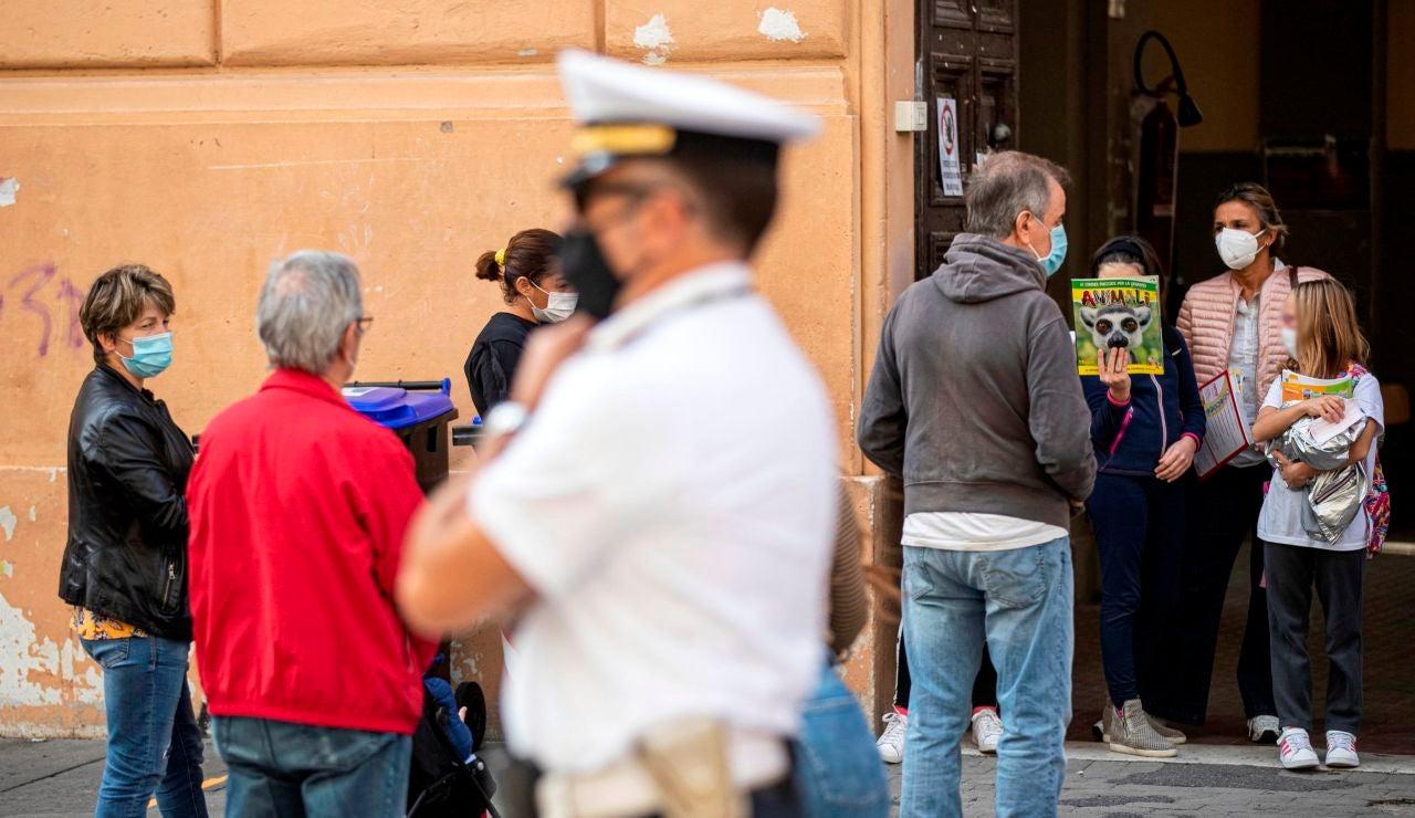 Italianos con mascarillas a la salida de un colegio en Roma