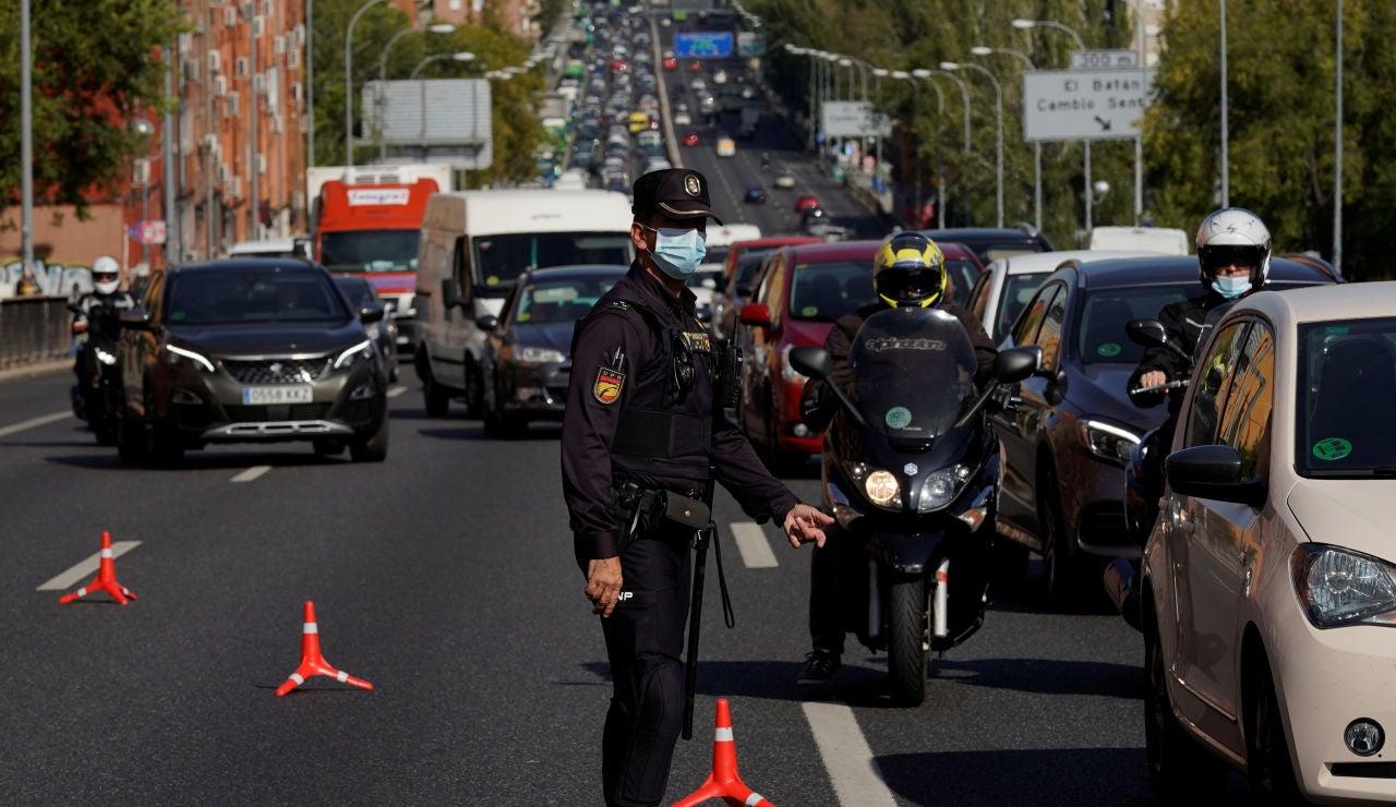 Un agente controla la movilidad en la salida de Madrid