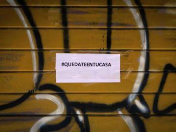 Imagen de un comercio cerrado con un cartel de Quedateentucasa
