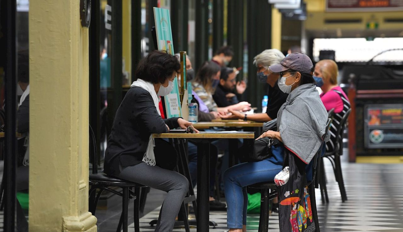 Ciudadanos con mascarilla tomando algo en una cafetería