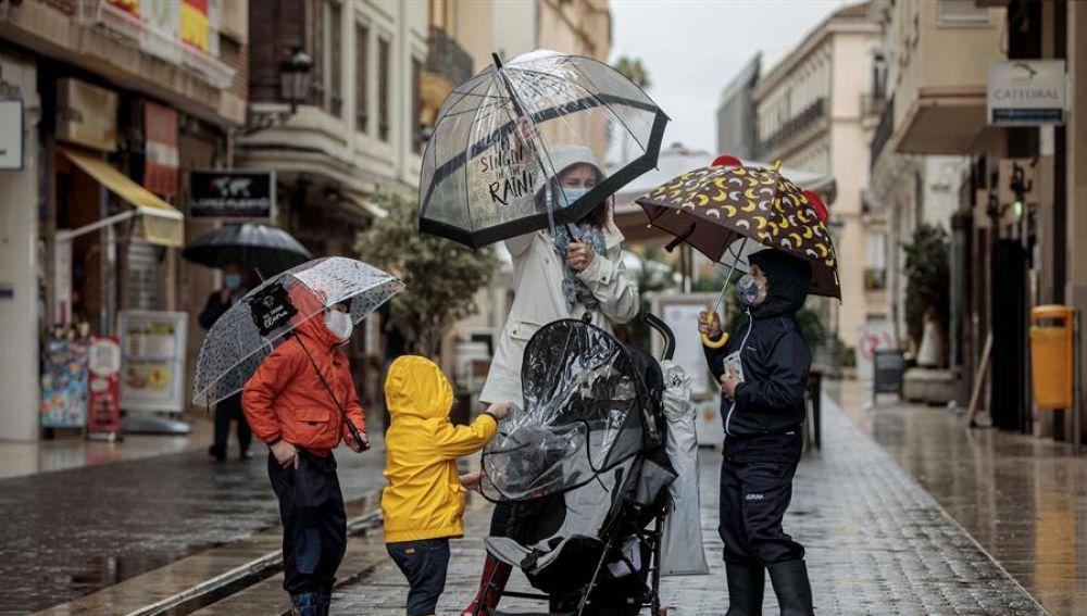 Una mujer con tres menores se protegen de la lluvia con paraguas y chubasqueros