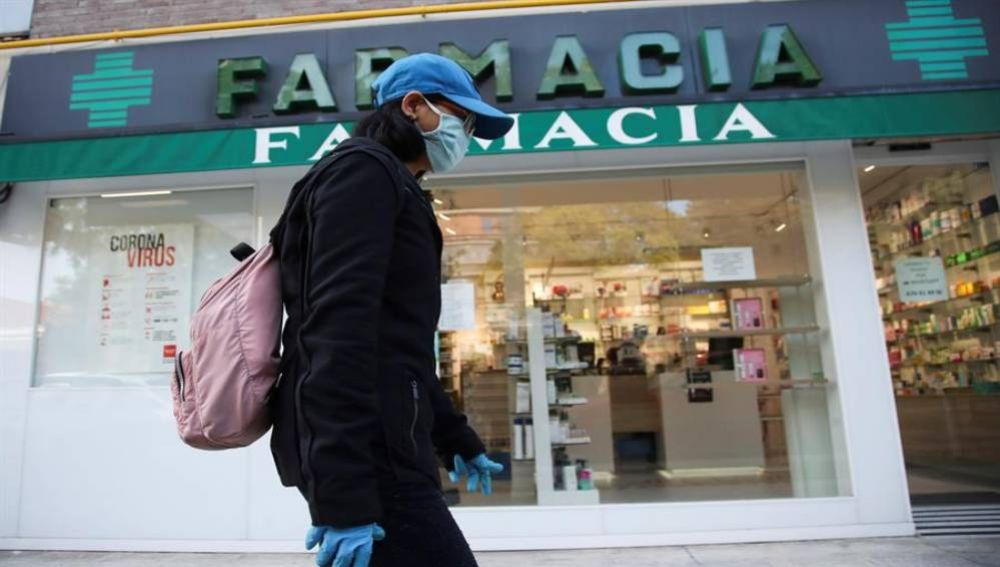 Una viandante, protegida con guantes y mascarilla, pasa por delante de una farmacia.