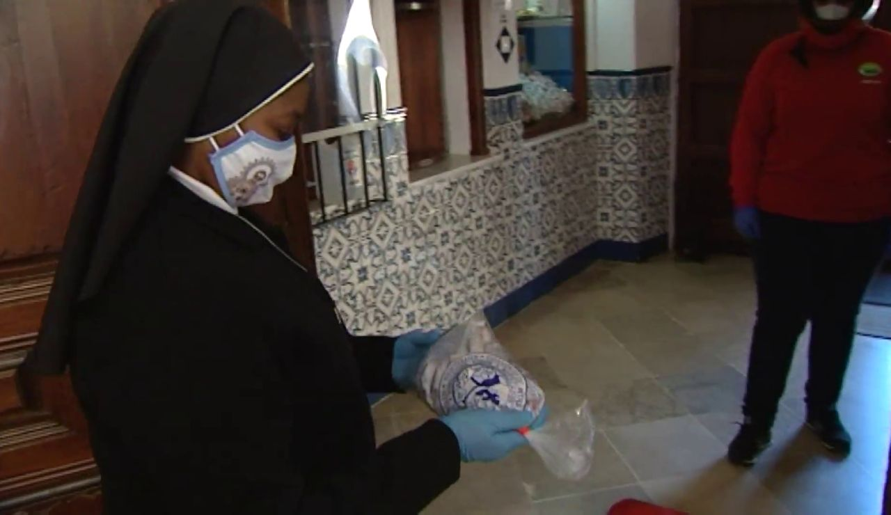 Una monja entrega un dulce navideño a un repartidor de Telepizza