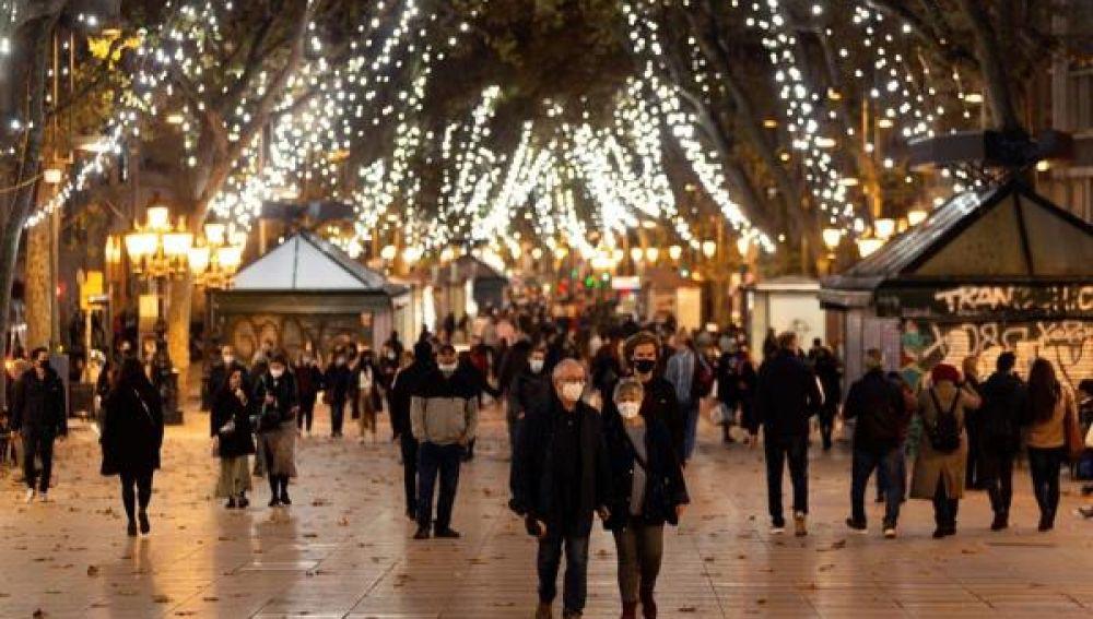 Gente paseando por el paseo Born en Barcelona con el encendido navideño