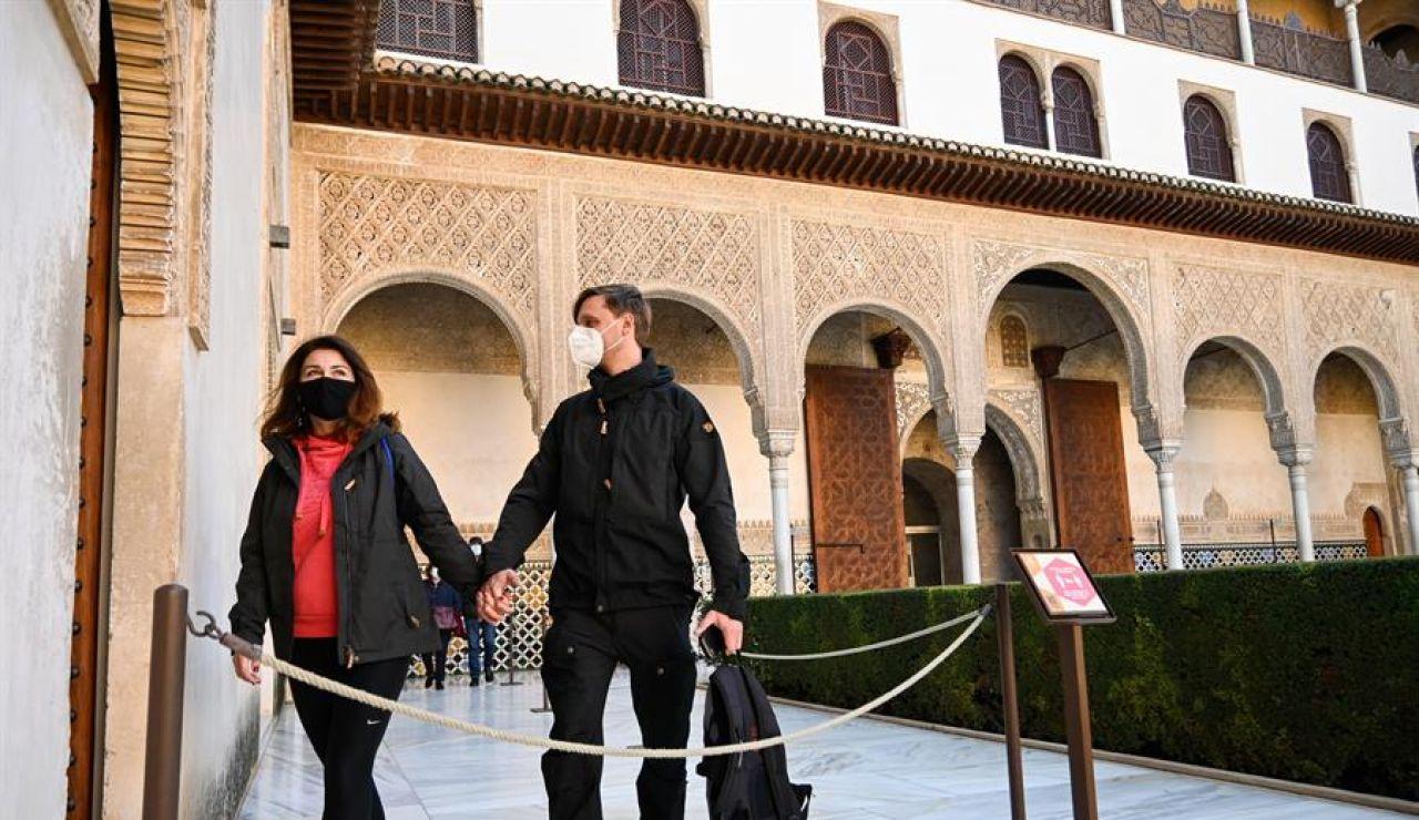 Dos turistas caminan por el interior de la Alhambra.