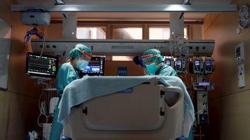 Dos médicos atienden a un paciente con coronavirus en un hospital.
