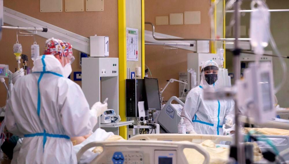 Médicos hablan con un paciente ingresado por coronavirus.