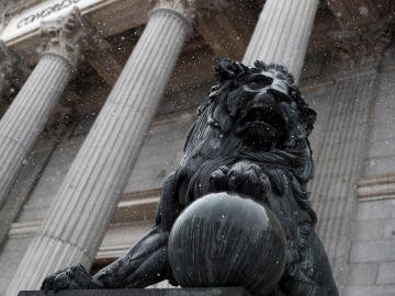 Los leones del Congreso de los Diputados con los primeros copos de nieve del día