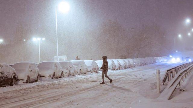 Una persona camina bajo una intensa nevada este viernes en la avenida Ramón y Cajal, en Madrid.