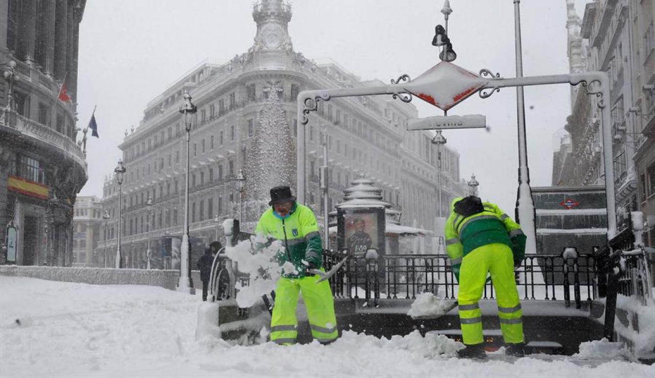 Operarios quitan la nieve en las cercanías a la Puerta del Sol de Madrid