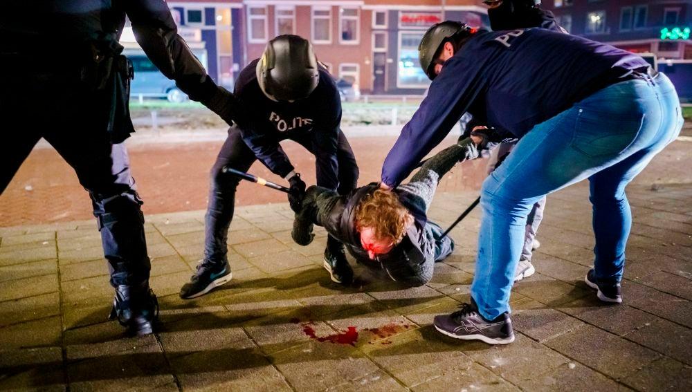 Un hombre es reducido por varios policías durante los distubios registrados anoche en Rotterdam, Países Bajos