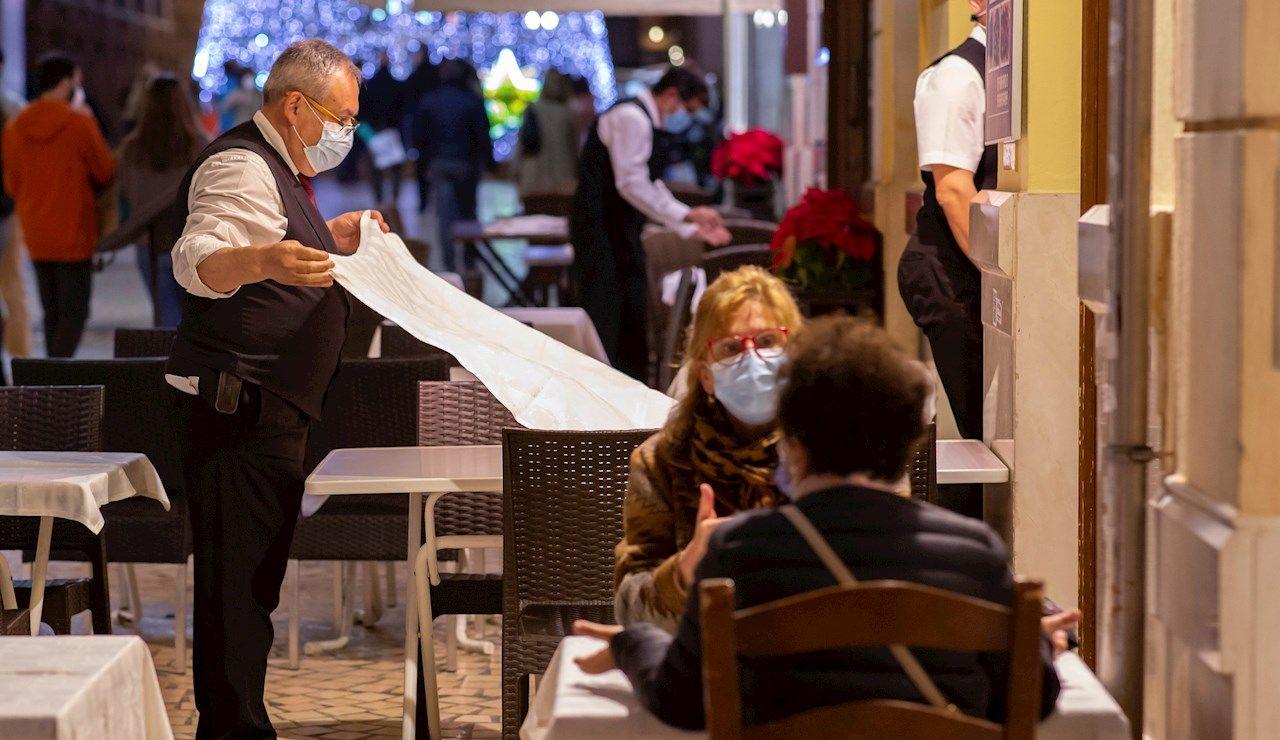 Varias personas con mascarilla en una terraza de Málaga