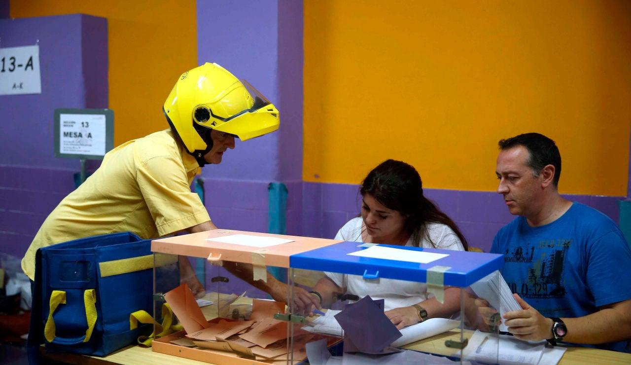 Elecciones Cataluña 2021: Un cartero entrega el voto por correo en una mesas electoral del Colegio Santa Marta de l'Hospitalet de Llobregat
