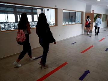 Varios estudiantes se dirigen a un aula por un pasillo en el IES Simone Veil de Paracuellos del Jarama, Madrid.