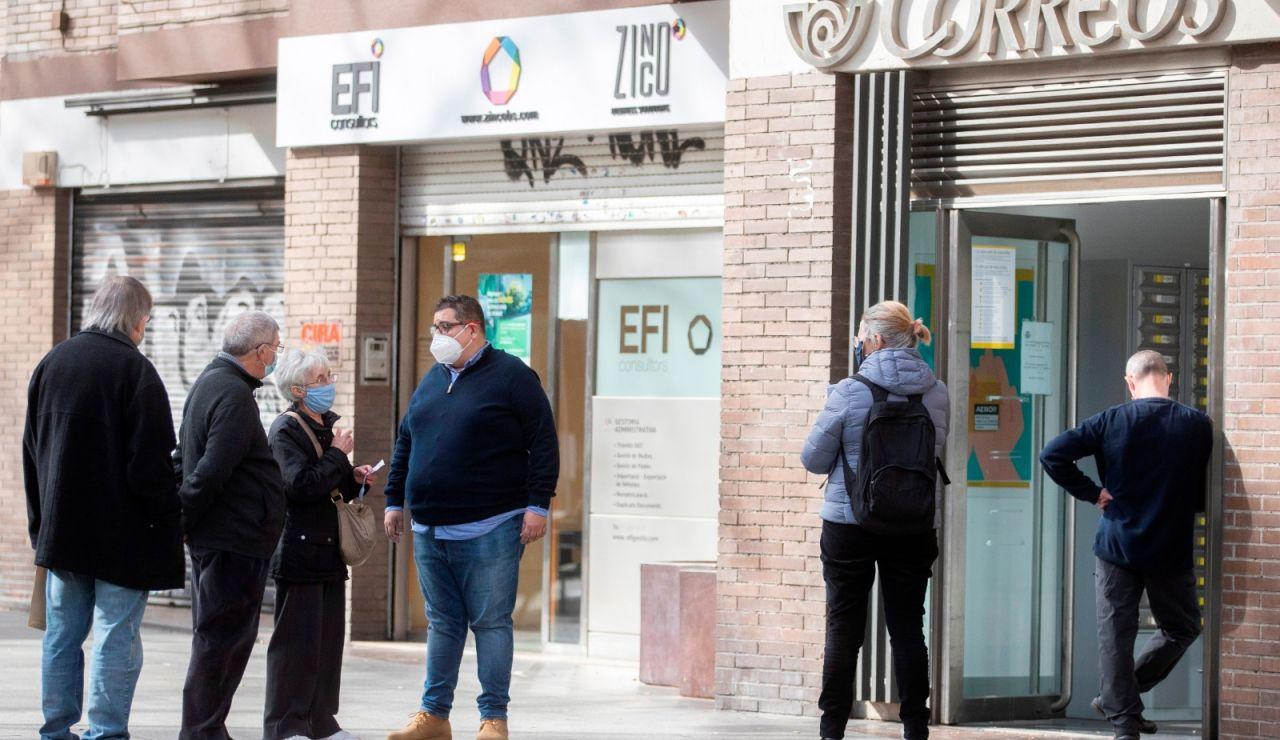 Varias personas hacen cola para votar por correo en las elecciones al Parlamento de Cataluña