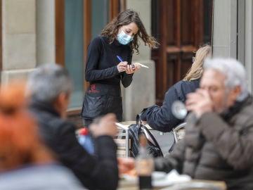 Una camarera atiende a varios clientes en una terraza el primer día de la apertura de la hostelería en Valencia