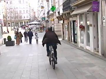 Un hombre circula en bicicleta por una calle en Ferrol