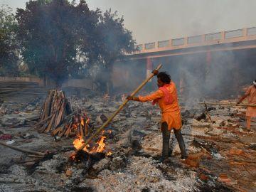 Un hombre quema cadáveres de fallecidos por coronavirus en India
