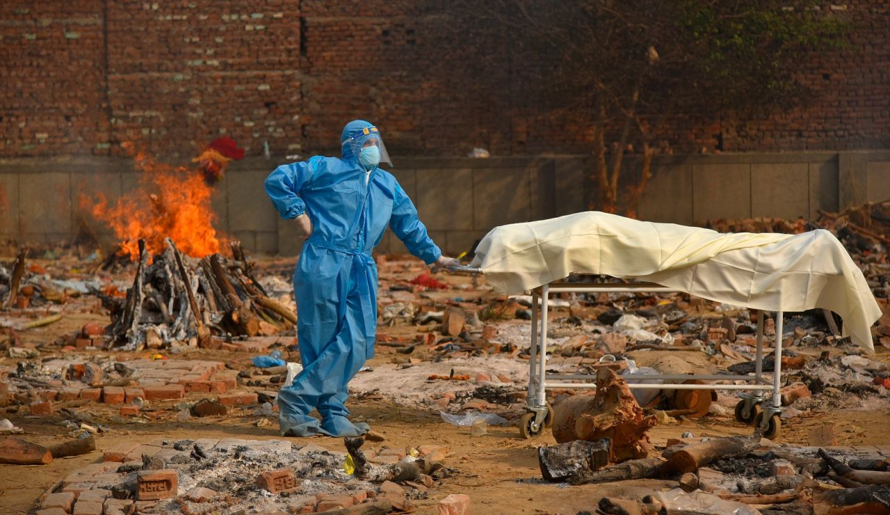 Un sanitario quema los cadáveres de muertos por COVID-19 en India