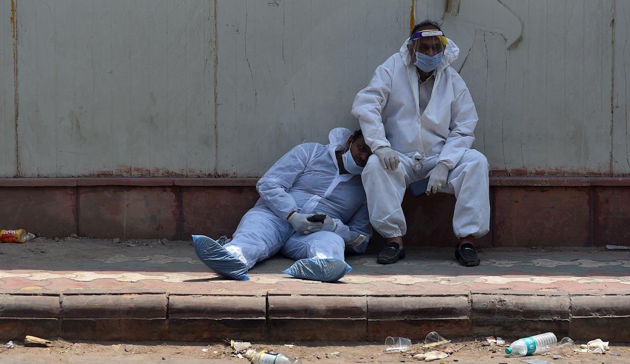 Dos paramédicos indios se toman un descanso a las puertas del depósito de cadáveres de un hospital en Nueva Delhi (India) este jueves