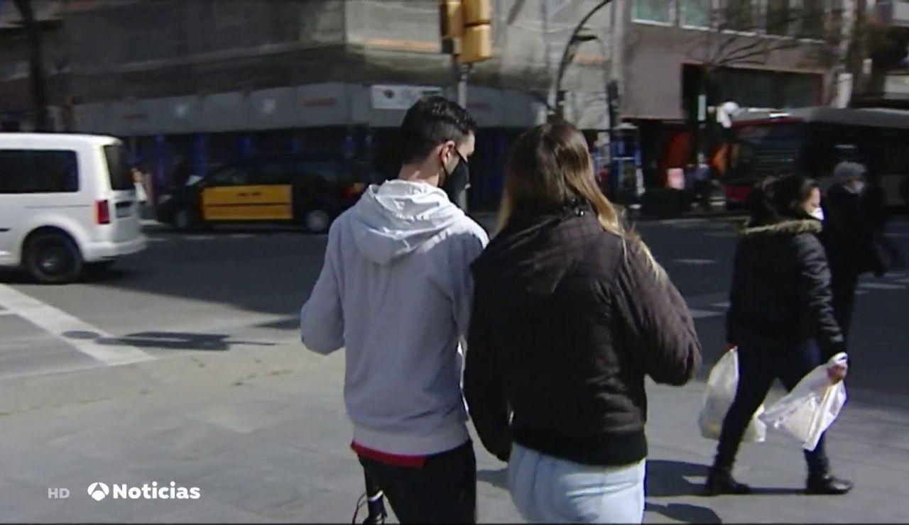 Dos jóvenes con mascarilla en la calle